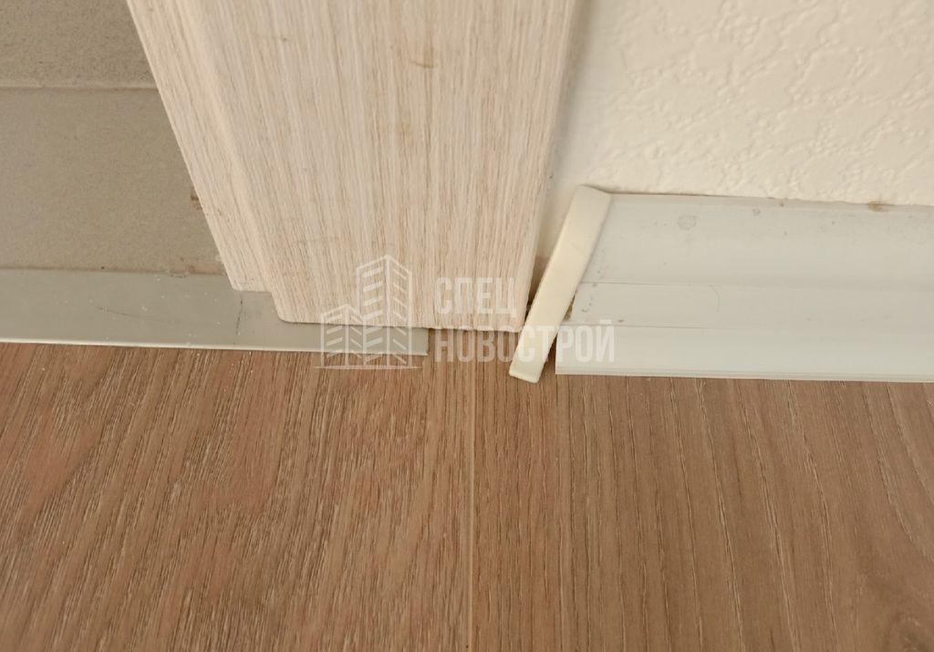 коротко подрезан плинтус, не закреплена торцевая заглушка плинтуса, некорректно подрезан порожек, наличник двери коротко подрезан и не примыкает к полу